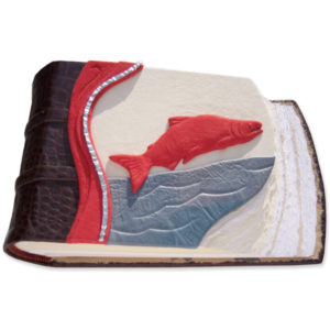 Sockeye Salmon Leather Scrapbook with carved red leather wrapped salmon sculpture over river on nature scene book cover