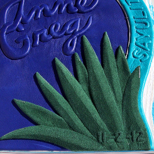 green leaf tropical plant sculpture embossed with green leather and wedding date on album cover, script embossed blue leather lettering, Mexico wedding book