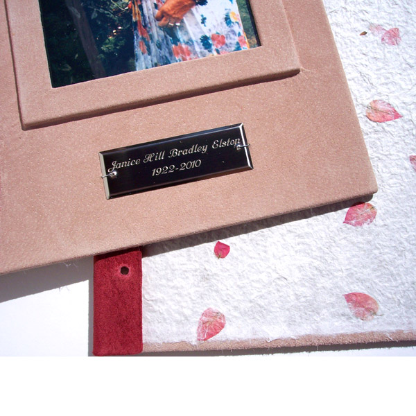 rectangular silver metal plate with engraved name and dates on pink leather book cover