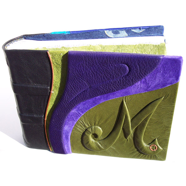 Embossed initial M under green leather on book cover with purple curved accents