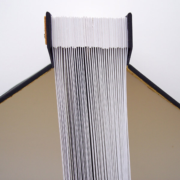 end view of screwpost book spine edge showing scrapbook pages with spacers