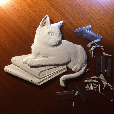 carving a cat resting on books to be custom pet album cover art